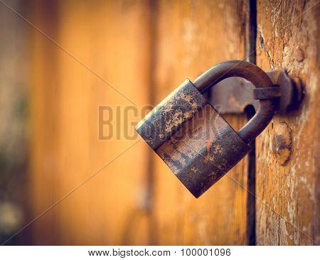 Old rusty lock on the vintage wooden door