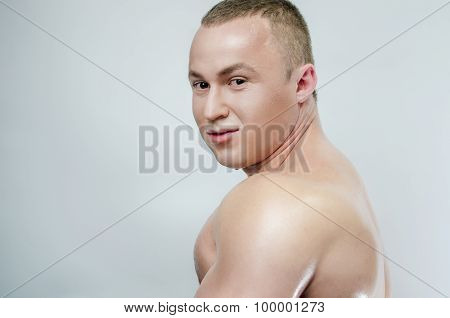 Bodybuilder in oil on a gray background