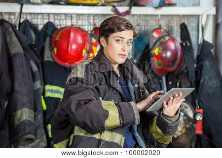 Portrait of confident firewoman in uniform using digital tablet at fire station
