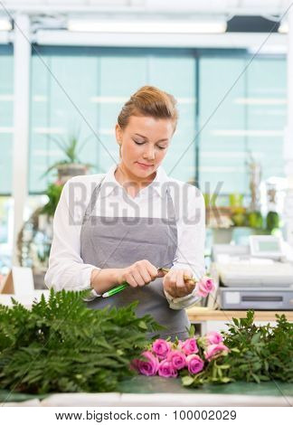 Female florist cutting stem on pink rose at counter in flower shop