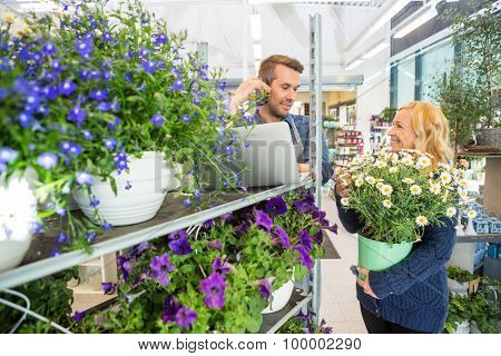 Smiling female customer with flower pot looking at florist using mobile phone in shop