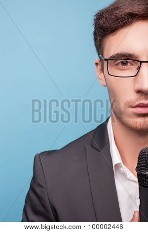 Attractive young male reporter is working with equipment