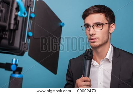 Cheerful young male journalist is reporting with seriousness