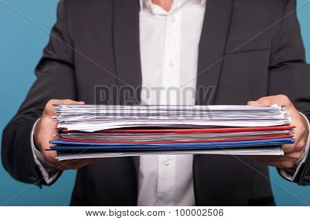 Young man in suit is working hard with papers