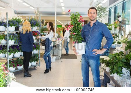 Portrait of confident man holding flower plant with florist assisting customer in background at shop