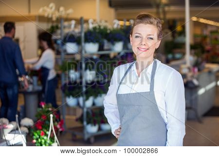 Portrait of smiling mid adult female salesperson at flower shop