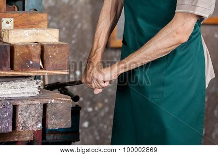 Midsection of male worker using paper press machine in factory
