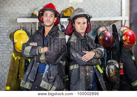 Portrait of confident young firemen standing arms crossed at fire station