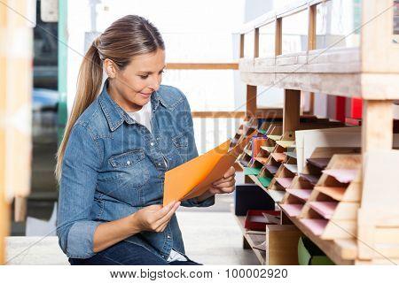 Smiling female customer choosing papers in shop
