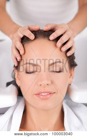 Attractive young woman has her hair washed in salon