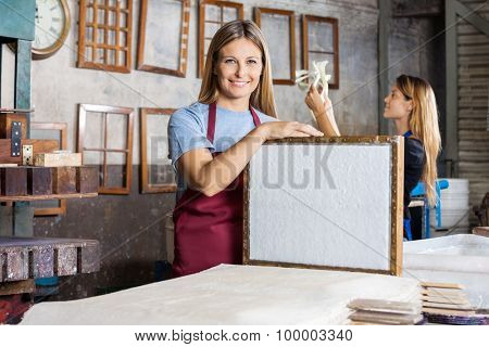 Portrait of happy mid adult female worker holding mold with paper in factory