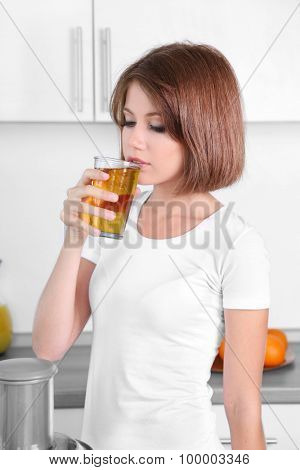 Young beautiful woman drinking apple juice