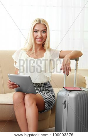 Woman with suitcase and tablet after traveling at home