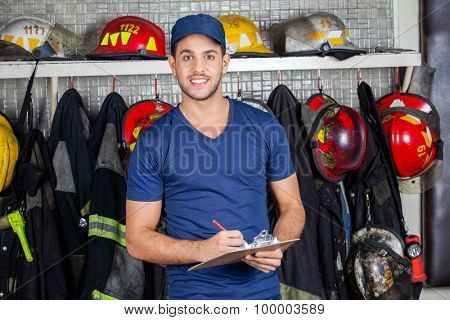 Portrait of confident male worker holding clipboard against uniforms hanging at fire station