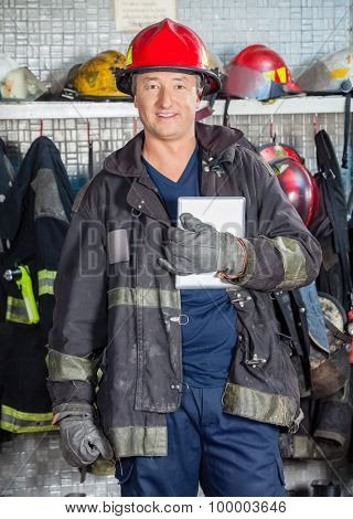 Portrait of smiling male worker holding digital tablet while standing at fire station