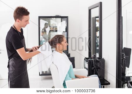 Attractive young hairstylist is serving his customer