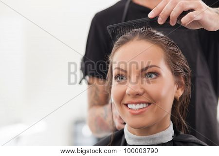 Attractive young girl is getting a haircut in salon