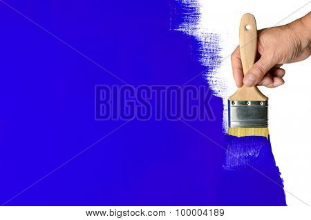 Man's hand using paintbrush with blue paint on wall