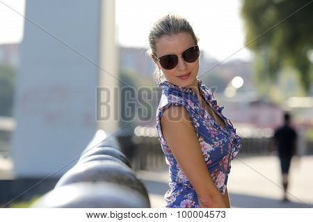 Young Beautiful Girl In Dark Glasses Standing Near Marble Columns
