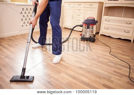 Cheerful young cleaner is doing housework with joy