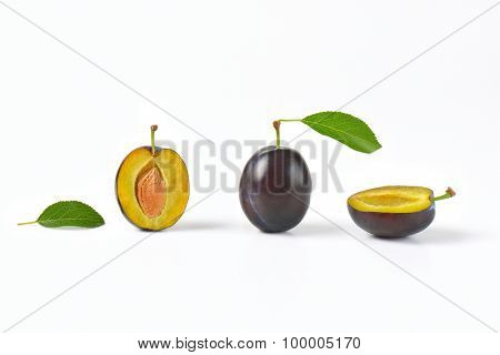 whole and halved plums on white background