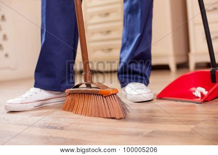 Skilled young male cleaner is cleaning floor in room