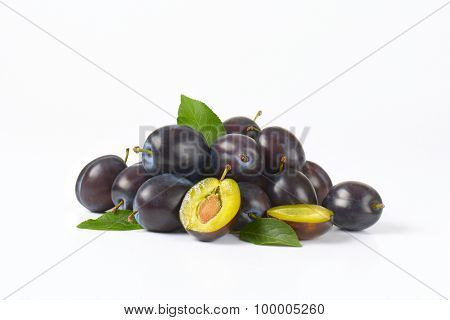 heap of ripe plums with leaves on white background