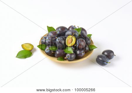 plate of ripe plums on white background