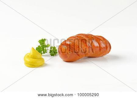 roasted sausage and mustard swirl on white background
