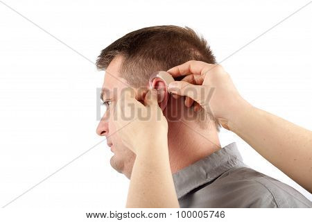 Audiologist inserting a hearing aid into a middle-aged man's ear - isolated on white poster