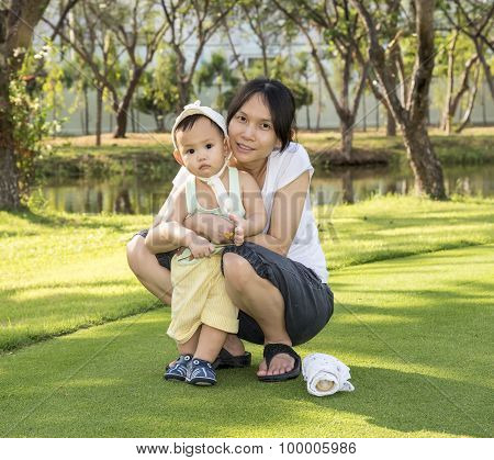 Mother Hold Baby When Family Picnic In The Park