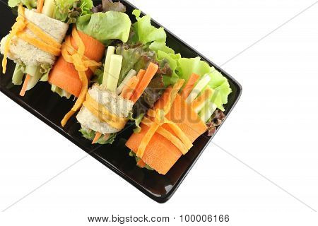 Roll Salad In The Black Dish On White.