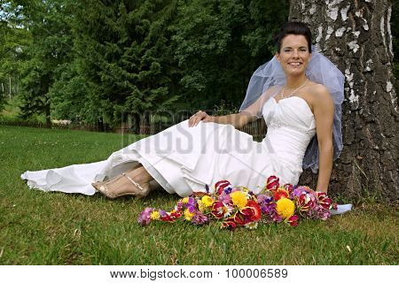 Young bride sitting under tree