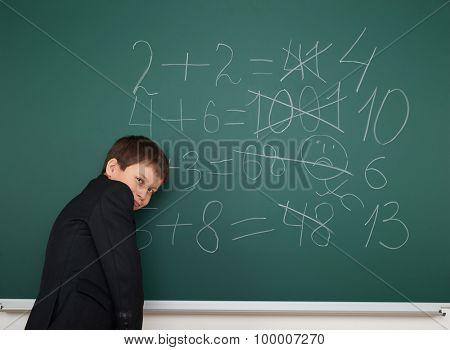 School boy solve math on the school board