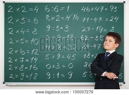 school boy solve math on board