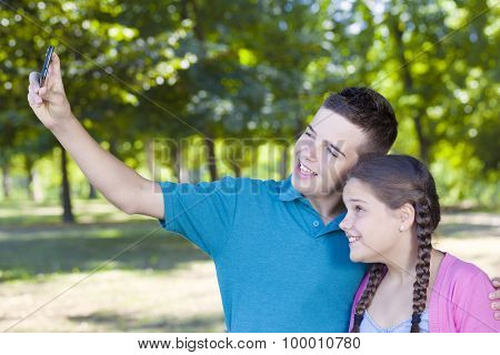 Happy smiling kids taking photos with smartphone outdoors
