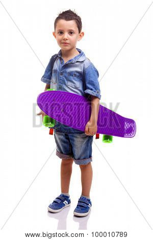 Schoolboy standing with a skateboard and backpack on white background