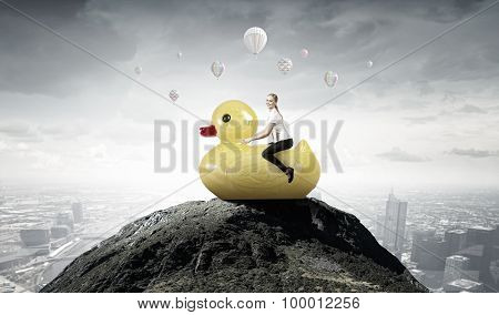 Businesswoman riding yellow rubber duck like child