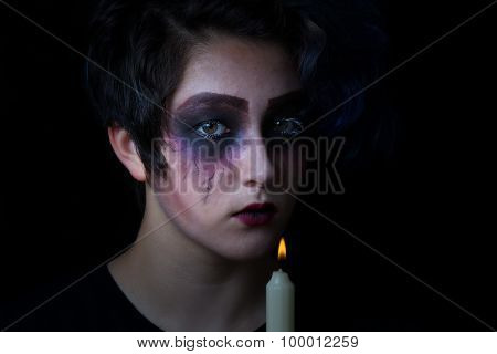Girl In Scary Makeup With Lite Candle On Black Background