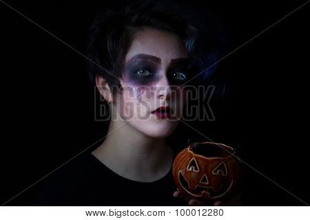 Girl In Scary Makeup With Pumpkin Container On Black Background