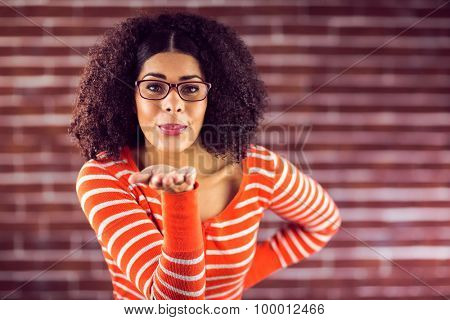 Portrait of attractive young woman sending kiss against red brick background