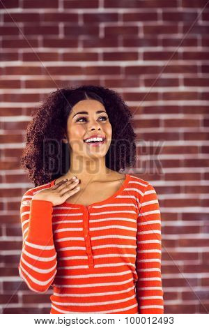 Surprised attractive young woman against red brick background