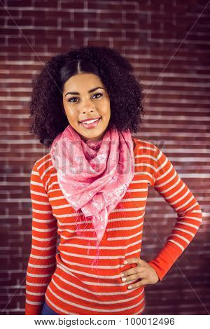 Portrait of smiling attractive young woman posing against red brick background