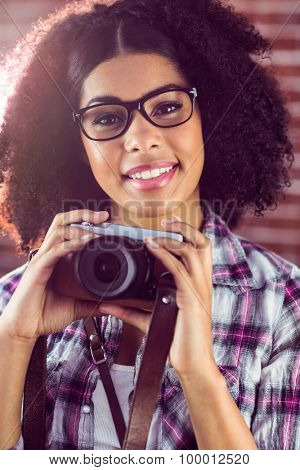 Portrait of attractive smiling hipster holding camera against red brick background