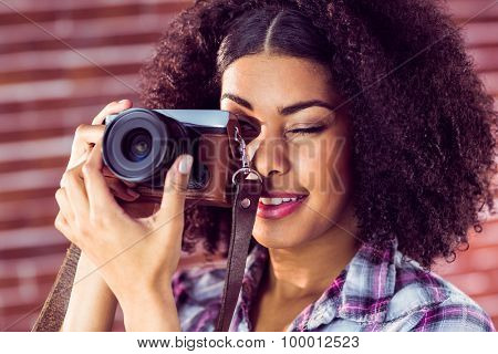 Attractive young woman photographing with camera against red brick background