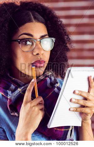 Portrait of attractive focused hipster taking notes against red brick background
