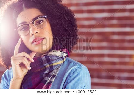 Portrait of attractive hipster thinking against red brick background