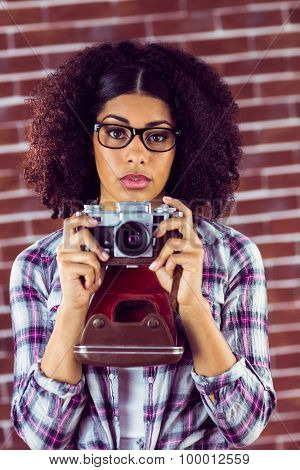 Portrait of attractive focused hipster photographing against red brick background