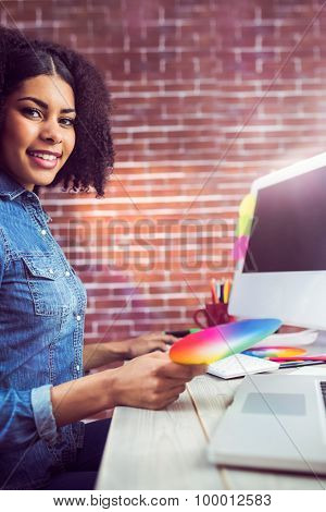Portrait of casual female designer smiling and holding colour chart against red brick background
