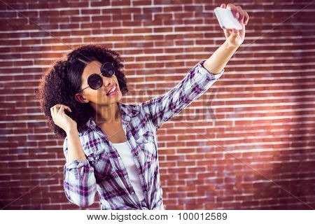 Attractive hipster taking selfies with smartphone against red brick background